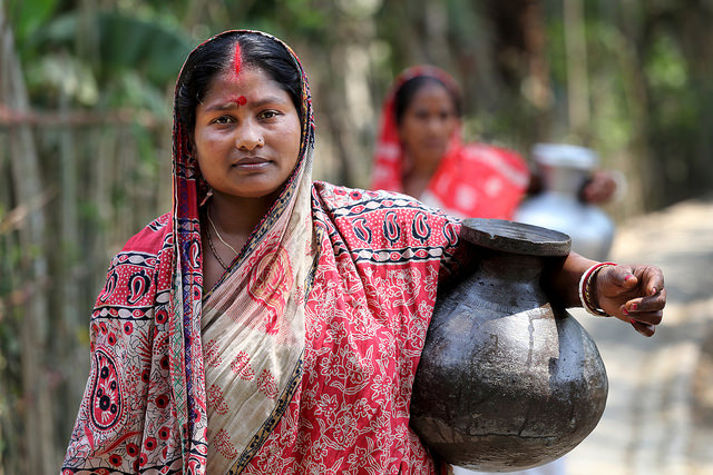 Komola Roy carrying drinking water in Fultola Village, Khulna, Bangladesh.