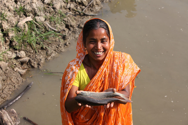 Woman showing fish caught from her pond in Khulna, Bangladesh.