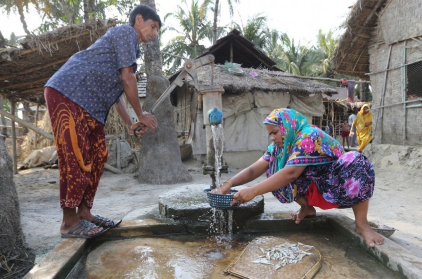A man helping his wife to clean fish in Jessore, Bangladesh.