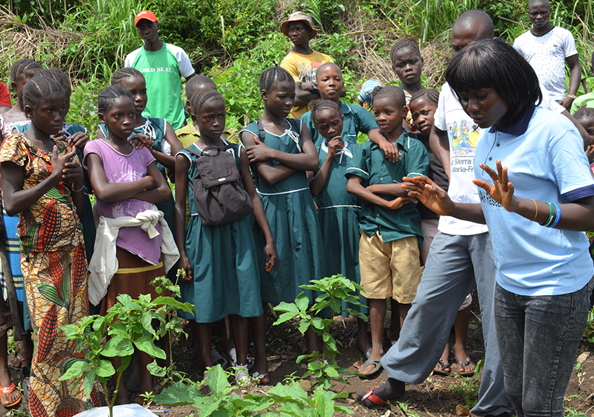 Yeanoh leads a hands-on learning activity with primary school students about benefits of producing and consuming fresh fish and vegetables to improve nutrition.